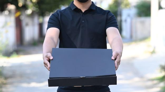 배달원 서비스가 출입구에서 피자 상자를 나르고 있습니다. 음식 배달 서비스입니다.