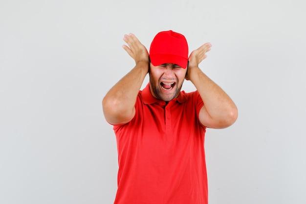 Uomo di consegna che grida e che tiene le mani sulle orecchie in maglietta rossa