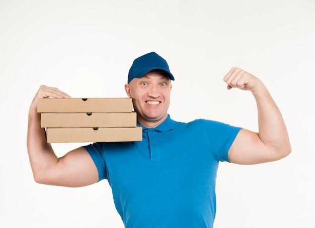 Доставка человек показывает бицепс во время переноски коробки для пиццы