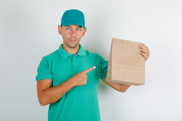 Delivery man showing brown paper bag in green t-shirt with cap