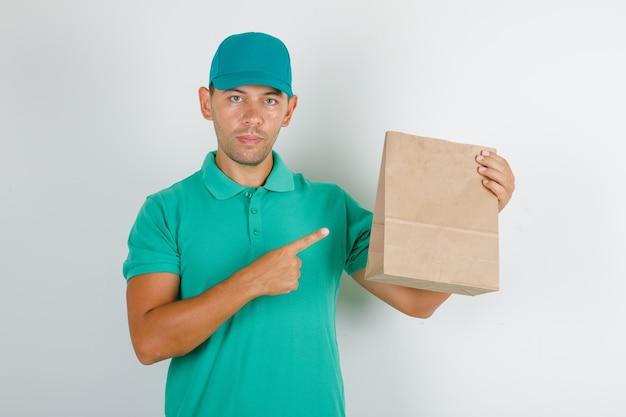Доставщик показывает коричневый бумажный пакет в зеленой футболке с кепкой