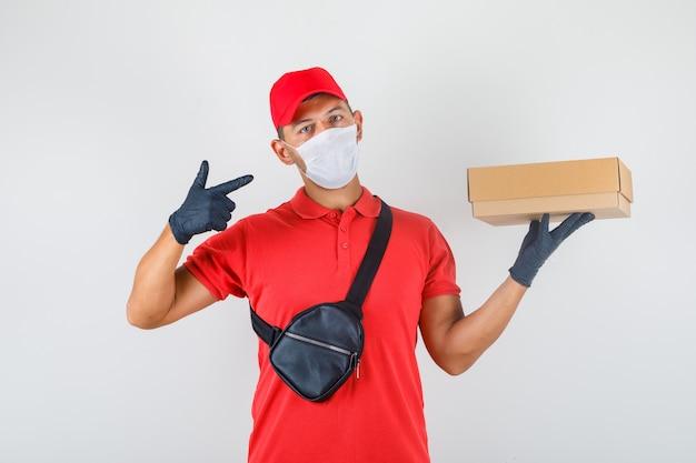 Uomo di consegna che mostra la scatola di cartone in mano in uniforme rossa, mascherina medica