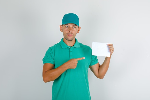 Delivery man showing envelope with finger in green t-shirt with cap