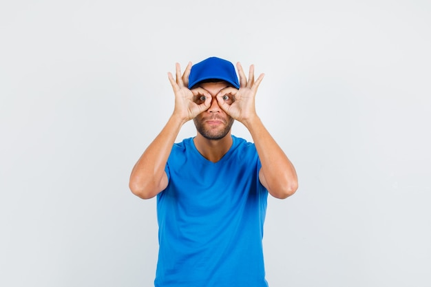 Delivery man showing glasses gesture in blue t-shirt
