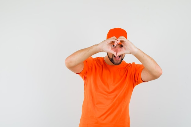 주황색 티셔츠, 모자를 쓰고 기뻐하는 모습을 보여주는 배달원. 전면보기.