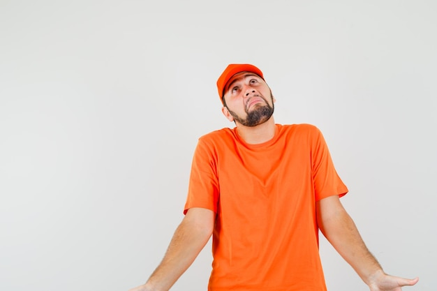 Delivery man showing helpless gesture by shrugging in orange t-shirt, cap and looking confused. front view.