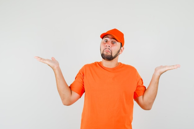 Delivery man showing helpless gesture in orange t-shirt, cap and looking confused. front view.