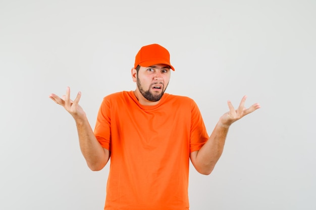 Delivery man showing helpless gesture in orange t-shirt, cap and looking confused , front view.