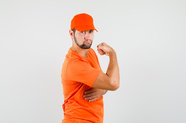 Delivery man showing his arm muscles in orange t-shirt, cap and looking confident , front view.