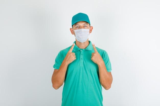 キャップ付きの緑のtシャツで彼の医療マスクを示す配達人