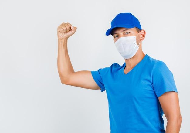 Uomo di consegna che mostra il muscolo in maglietta blu
