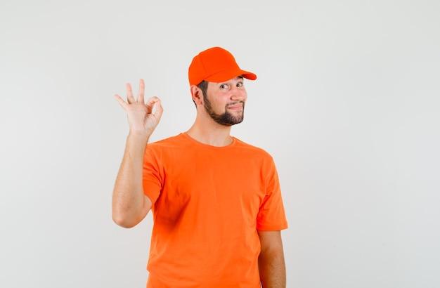 Fattorino che mostra segno ok in maglietta arancione, berretto e sembra allegro. vista frontale.