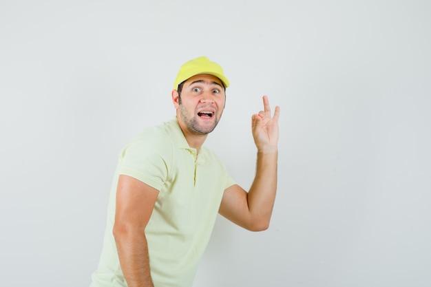 Uomo di consegna che mostra segno giusto in uniforme gialla e che sembra felice. vista frontale.