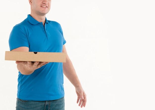 Доставка человек показывает коробку с пиццей в руке