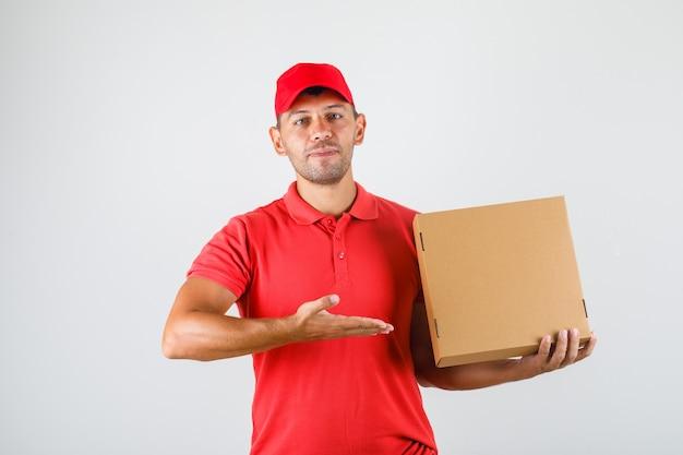 赤い制服を着た彼の手でピザの箱を示す配達人