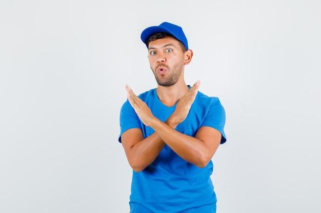 Uomo di consegna che mostra il gesto di rifiuto in maglietta blu