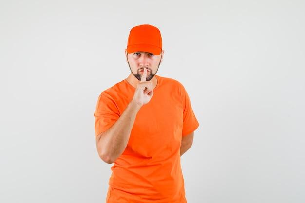 オレンジ色のtシャツ、キャップで沈黙のジェスチャーを示し、注意深く見ている配達人。正面図。