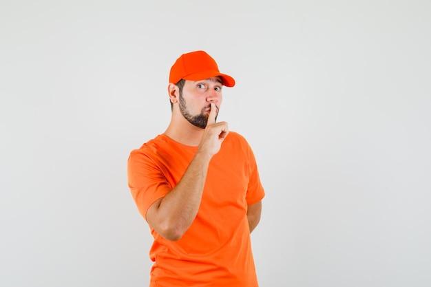 Uomo di consegna che mostra gesto di silenzio in maglietta arancione, berretto e guardando attento. vista frontale.