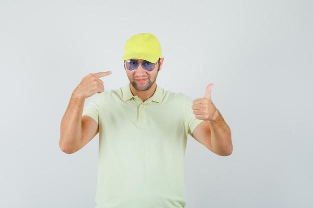 Fattorino che mostra il pollice in su indicando gli occhiali in uniforme gialla e guardando fiero, vista frontale.