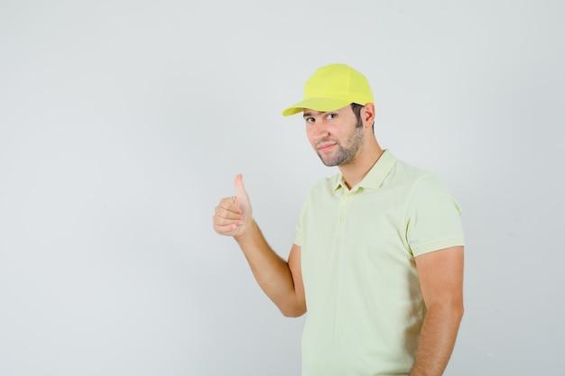 Uomo di consegna che mostra il pollice in su in uniforme gialla e sembra ragionevole, vista frontale.