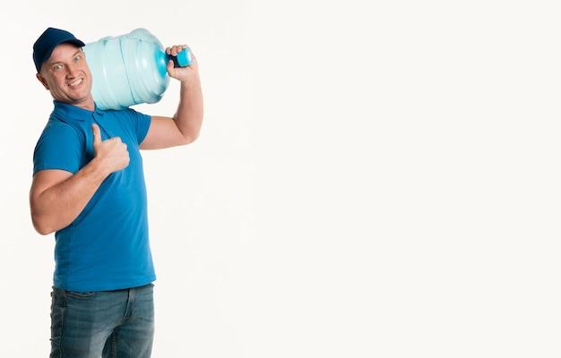 Доставка человек показывает палец вверх и несет бутылку с водой