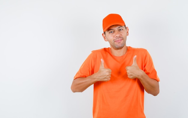 Delivery man showing thumbs up in orange t-shirt and cap and looking cheerful