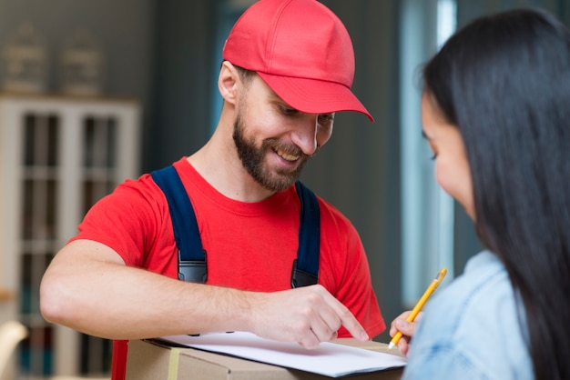 Delivery man showing woman where to sign to receive order