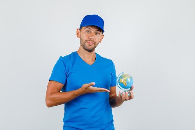 Uomo di consegna che mostra il globo del mondo in maglietta blu