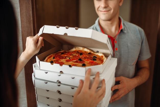 配達人はドアで女性客に新鮮で熱いピザを示しています