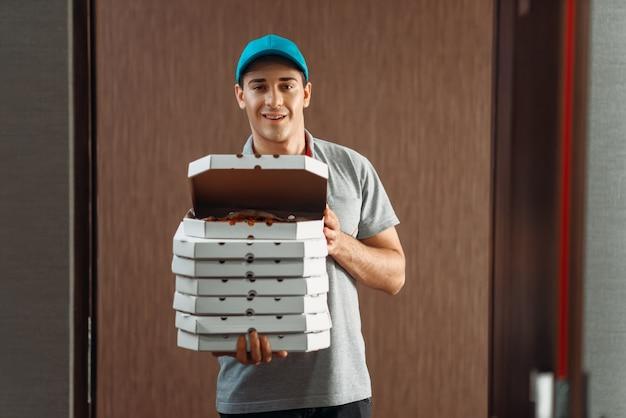 配達人は新鮮なピザを示し、サービスを提供します
