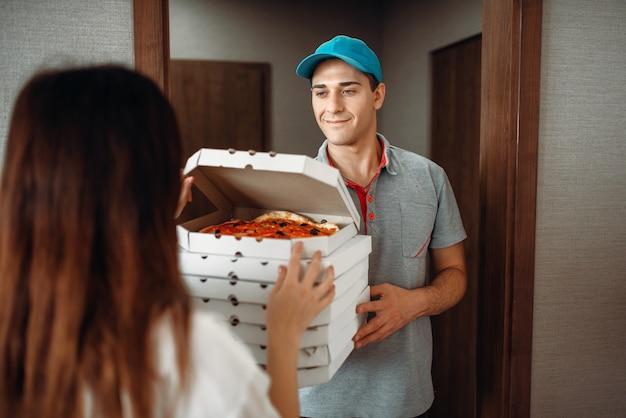 配達人はドアで顧客にピザを示しています