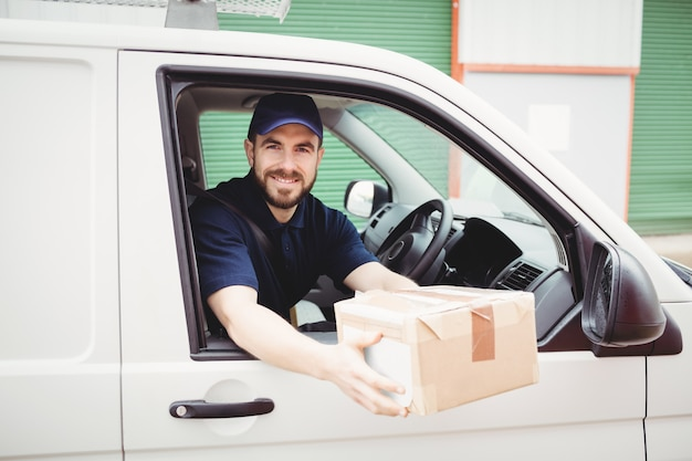 Delivery man sitting in his van while holding a package