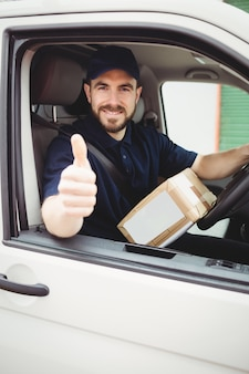 Delivery man sitting in his van with thumbs up