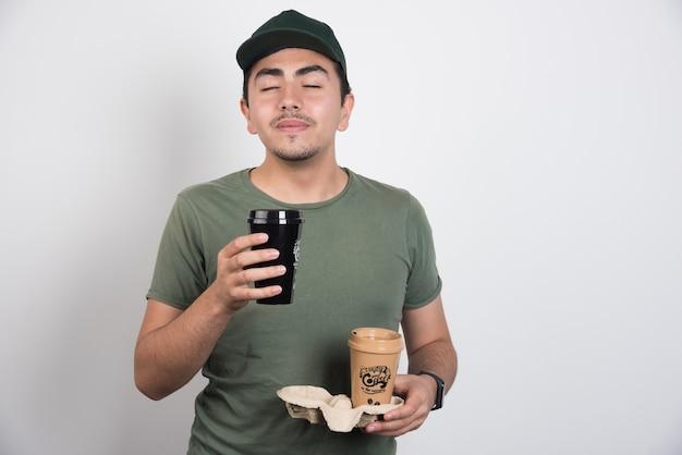 흰색 바탕에 커피의 향기를 냄새 맡는 배달 남자.