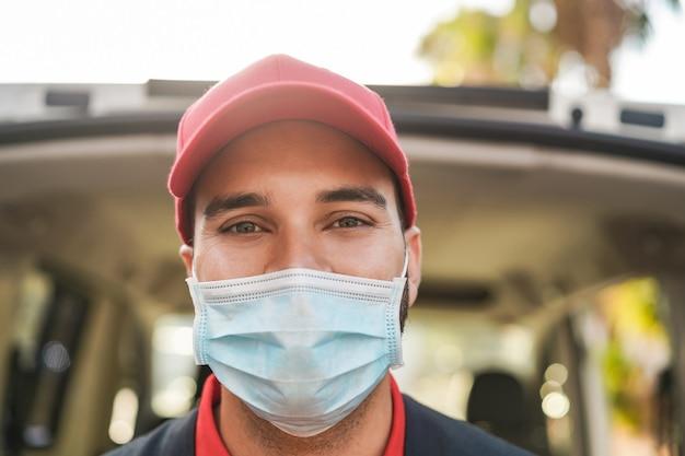 안전 마스크를 착용하는 동안 카메라에 웃 고 배달 남자
