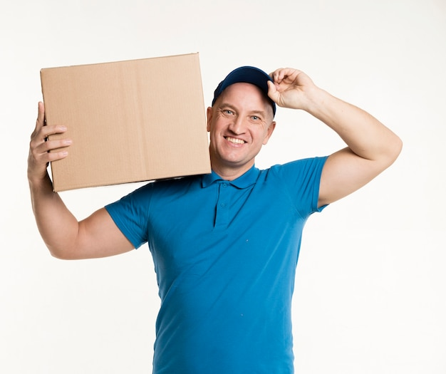 Delivery man smiling and posing with cardboard box on shoulder