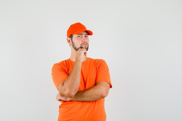 オレンジ色のtシャツ、キャップ、賢明な、正面図でポーズを考えて立っている配達人。