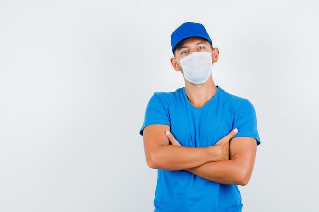 青いtシャツで腕を組んで立っている配達人
