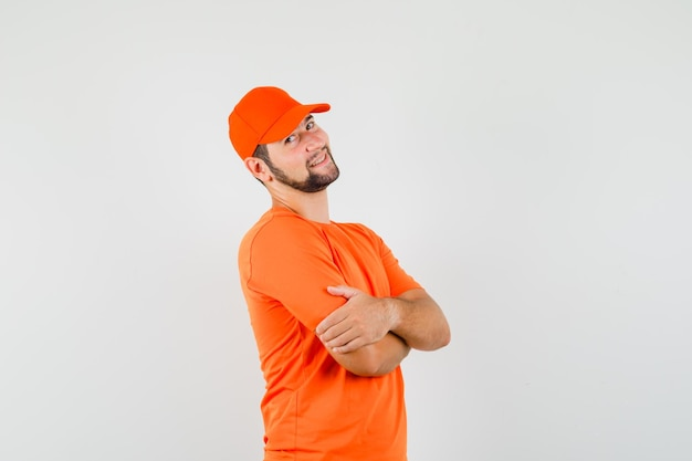 オレンジ色のtシャツ、キャップ、嬉しそうに腕を組んで立っている配達人。正面図。