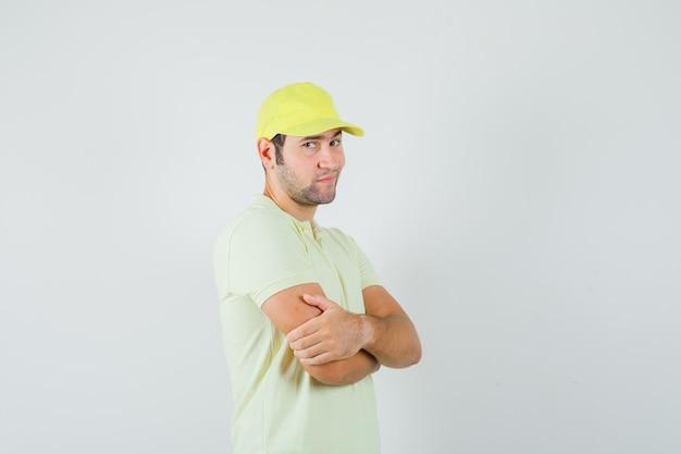 黄色い制服を着た腕を組んで立っていて、賢明に見える配達人。正面図。