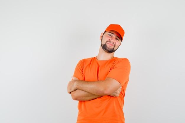 Fattorino in piedi con le braccia incrociate in maglietta arancione, berretto e sembra allegro. vista frontale.