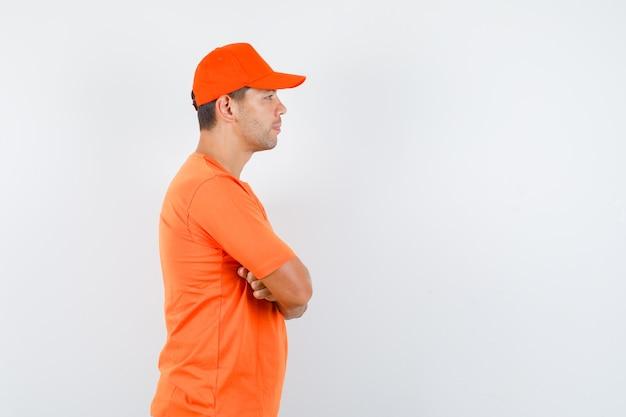 Fattorino in piedi con le braccia incrociate in maglietta arancione e berretto e guardando concentrato. .