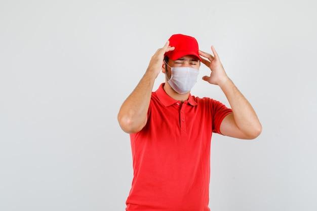 赤いtシャツで頭痛に苦しんでいる配達人