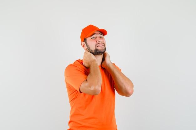 オレンジ色のtシャツ、キャップで首の痛みに苦しんでいる配達人と疲れているように見えます。正面図。