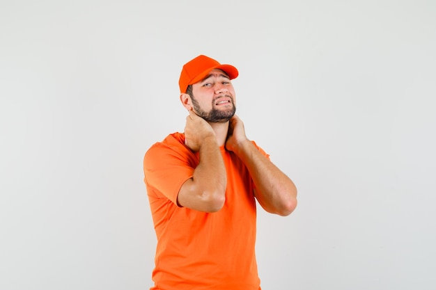 Delivery man suffering from neck pain in orange t-shirt, cap and looking fatigued. front view.