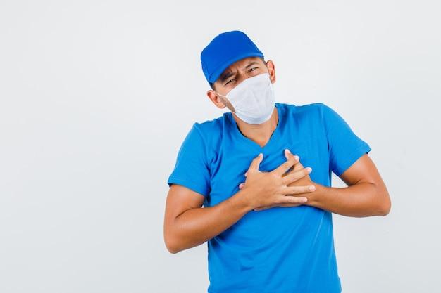 파란색 티셔츠에 가슴 통증으로 고통받는 배달 남자