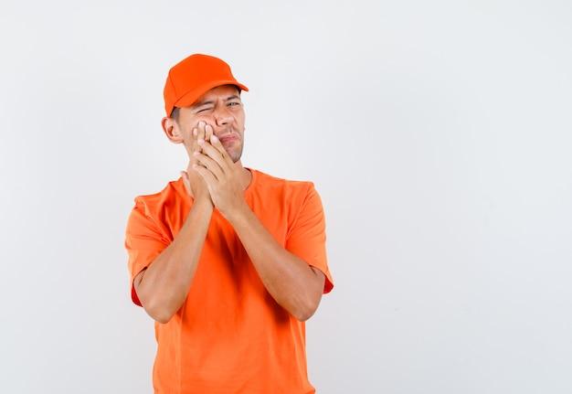 Fattorino che soffre di mal di denti in maglietta arancione e berretto e sembra turbato