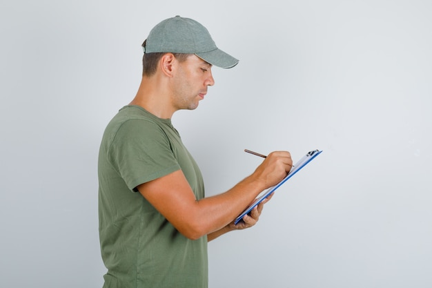 Delivery man taking notes on clipboard in army green t-shirt, cap and looking busy .