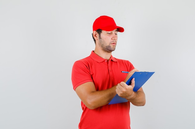 Delivery man taking notes on clipboard in red t-shirt