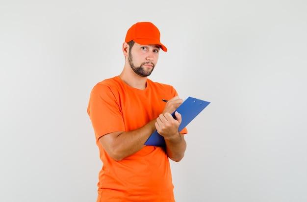 オレンジ色のtシャツ、キャップ、賢明な外観、正面図でクリップボードにメモを取る配達人。